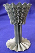 Photograph of origami goblet. It has a circular base with a stem and decorative cup on top.