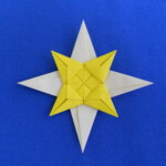 Photograph of origami star of Bethlehem. It has four large white points and four smaller yellow points with a decorative center.